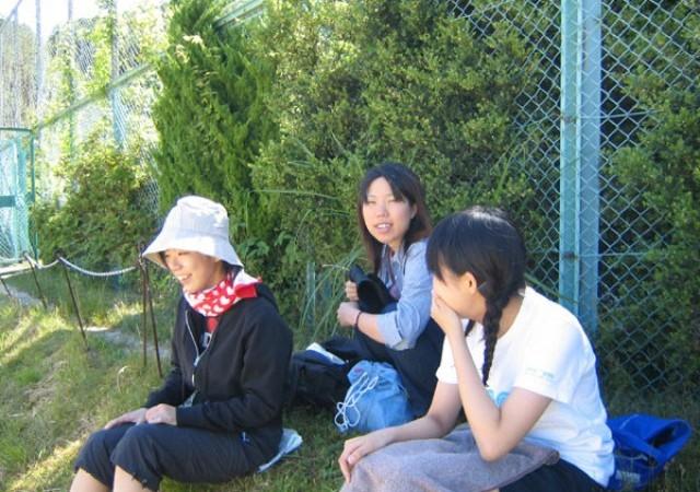 観戦風景1: 比叡グラウンドには陽射しを遮って観戦する設備がありません。フェンス際にできた日陰で観戦しているところ。小田さんの帽子と首に巻いたタオルが陽射しの強さを物語ってますね。