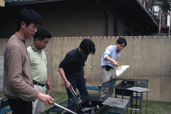 只今準備中-: 男性陣編-炭火をおこすのは男性陣の仕事。うまく火を起こすには団扇の扇ぎ方にコツがあるんですね。これ、吉田助教授が異様に上手いです。