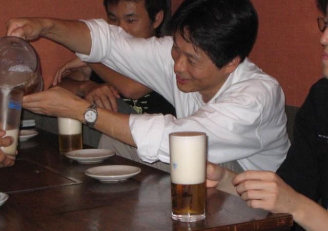 飲み会の様子1 吉田さんが手づからビールを注いでくださっています。