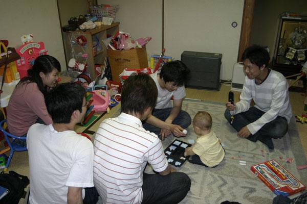 浅田さんのお子さんを囲んで。 かわいらしい仕草にみんなの顔も自然とほころんでいます。